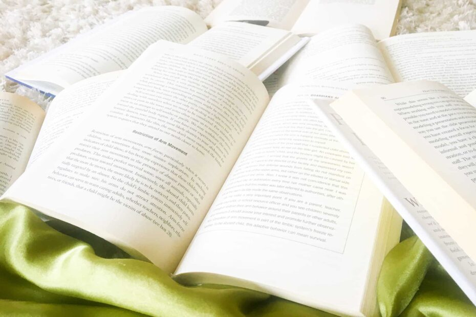 Open books stacked on top of each other laying on the floor