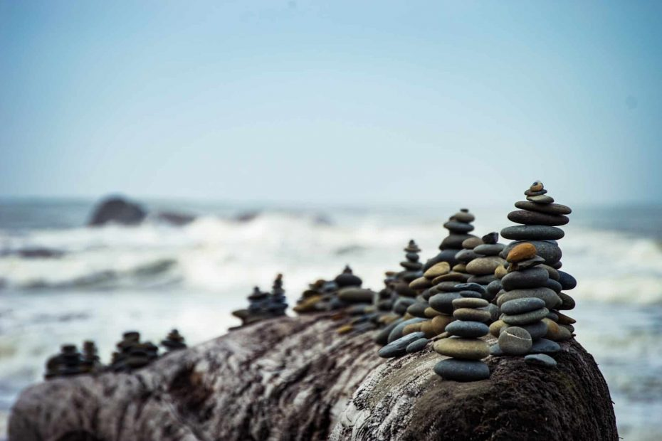 Beautifully stacked stones on a rock on the ocean. Tranquility aids a healthy mind healthy body experience.