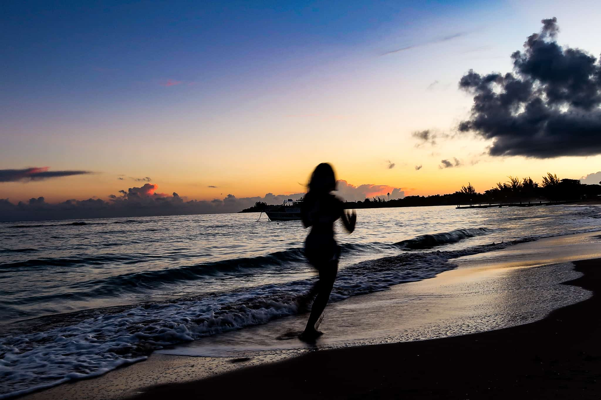female silhouette running on the beach to keep fit