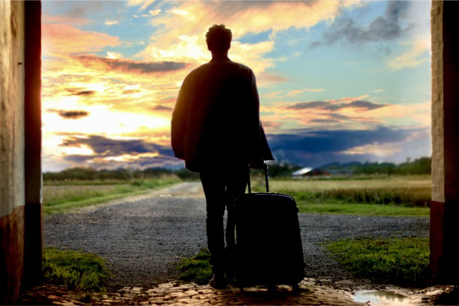 A silhouette pulling a luggage into an open field showing that it's easy to pack light when traveling