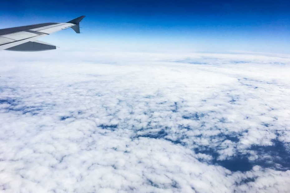 Cloud filled sky with a tip of a passenger plane wing showing a cheap way to travel