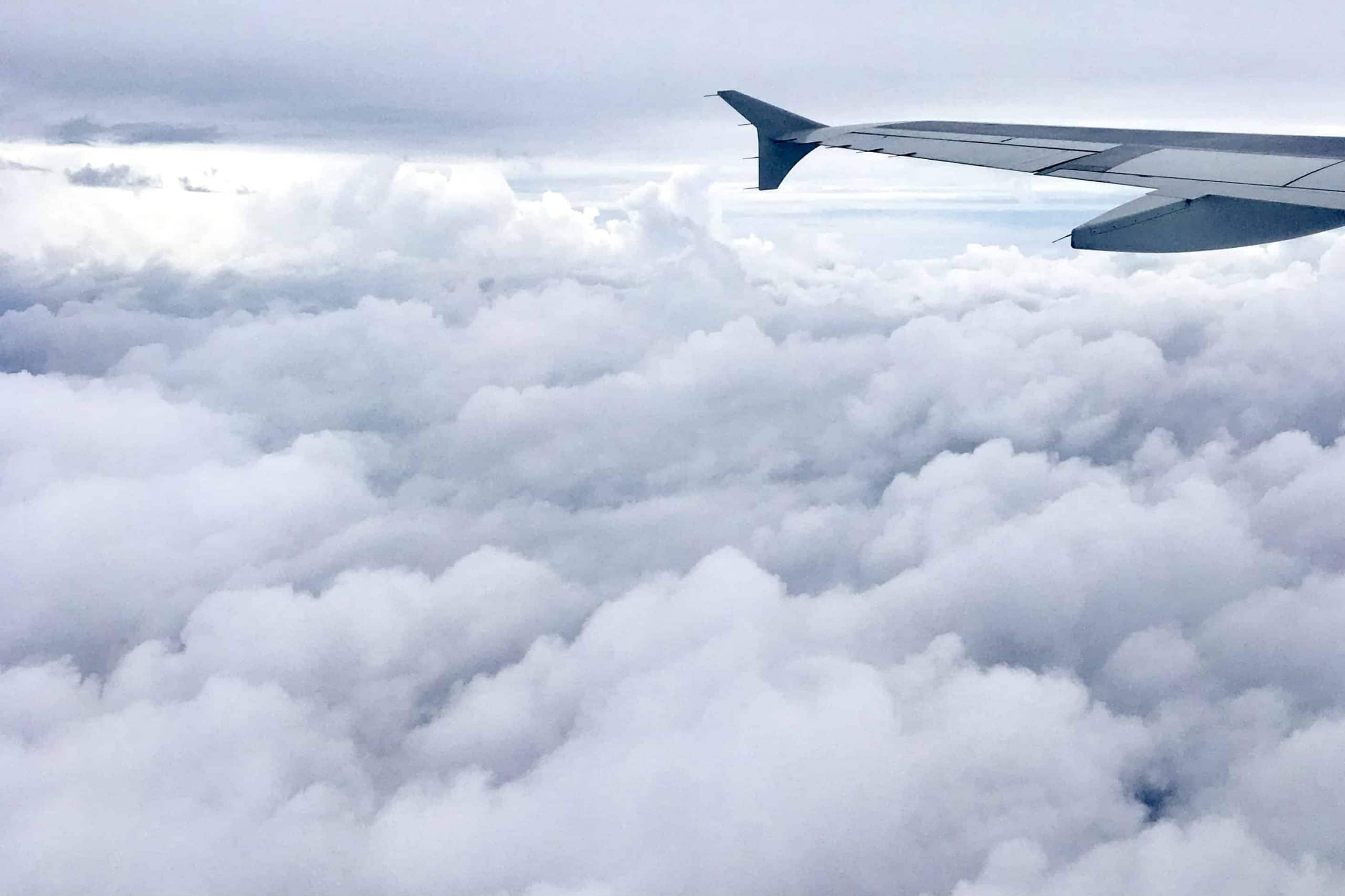 Cloudy sky under a plane wing