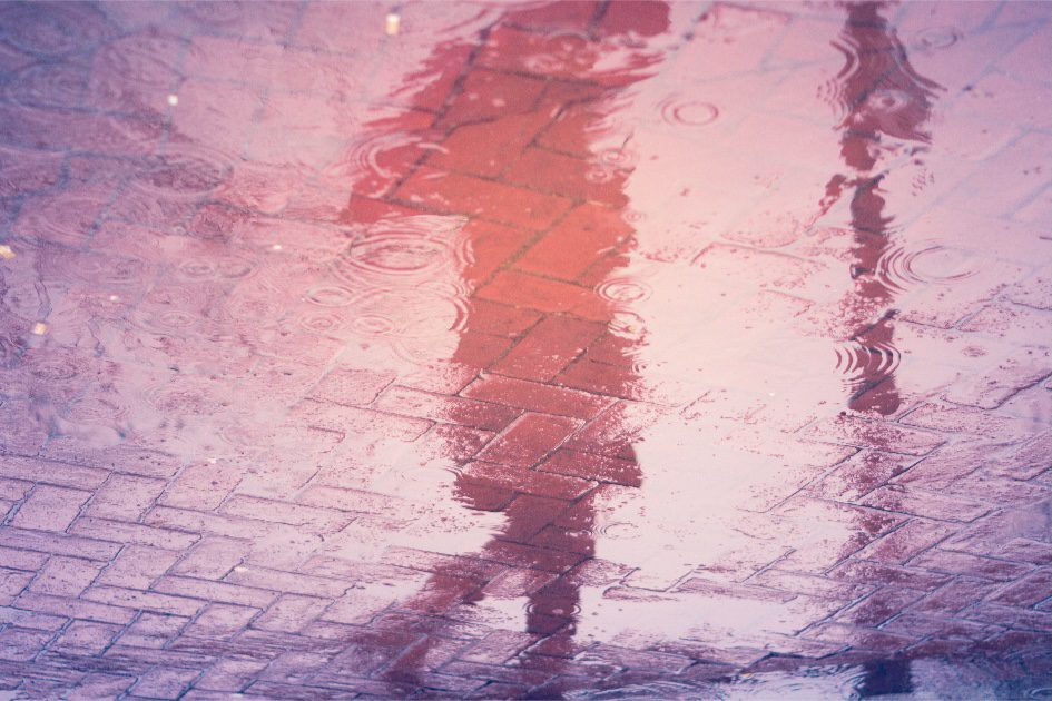 the water reflection of a shadow figure walking alone under an umbrella on a rainy night