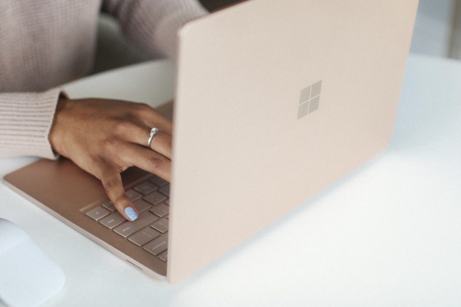 woman's hand on a laptop searching for travel safety tips and requirements