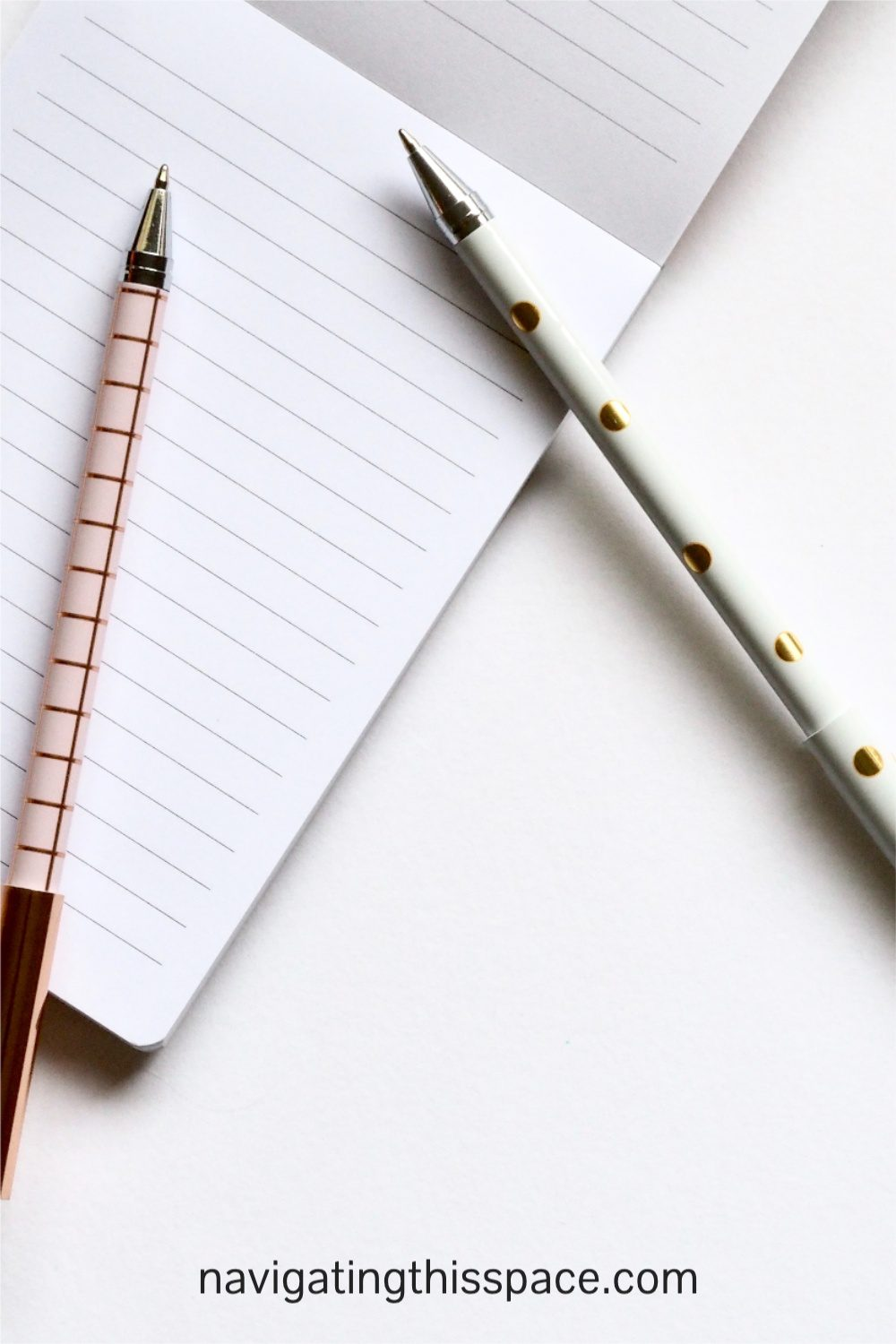 two pens and a blank notebook